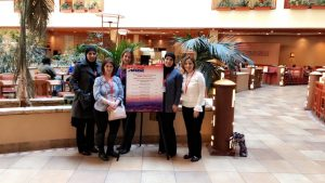 EL and SIP team members pose next to a NABE conference sign